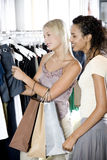 Two young women shopping for clothes Royalty Free Stock Photos