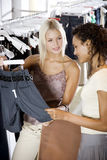 Two young women shopping for clothes Stock Images