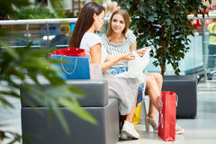 Two Young Women Shopping for Clothes. Portrait of two beautiful young women in shopping mall relaxing on sofa with paper bags, discussing clothes bought on sale Stock Photo