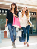 Two young women shopping at the mall royalty free stock images