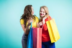 Two young women shopping with multicolored bags. Show each other the purchase Royalty Free Stock Photography