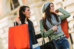 Two young women during shopping spree holding bags and smiling Royalty Free Stock Photos