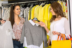 Two Young Women Shopping in a Store. Choosing clothes Royalty Free Stock Photography