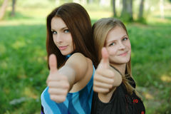 Two young women showing Royalty Free Stock Images