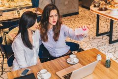 Two young women sit in a cafe at a table in front of a laptop and do selfie on a smartphone. Meeting two friends Stock Photos