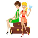 Two young women sit on suitcases Royalty Free Stock Photos