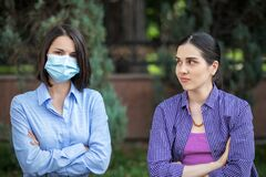 Free Two Young Women Sits On A Park Bench. One Woman Wearing A Mask, One Without A Mask. Different Attitudes To Pandemic. Royalty Free Stock Photos - 208198958