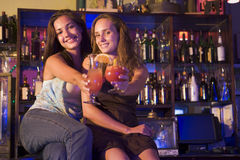 Two young women sitting on a bar counter, toasting stock images