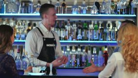 Two young women sitting at bar, talking with a bartender, the second bartender is coming stock footage