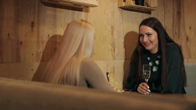 Two young women sitting in a cafe drinking champagne and talking. stock video