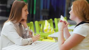 Two young women sitting at the cafe and talking. Female friends talking in cafe stock video