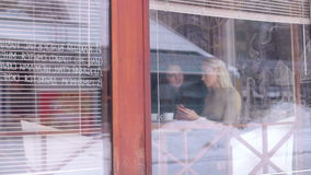 Two young women sitting in cafe. View from the street through the glass. HD stock video