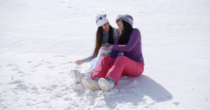 Two young women sitting chatting in the snow Stock Photo
