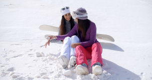 Two young women sitting chatting in the snow Stock Images
