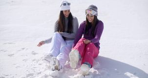 Two young women sitting chatting in the snow. Two young women sitting side by side chatting and laughing in the snow at an alpine ski resort smiling as they stock footage