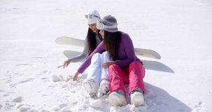 Two young women sitting chatting in the snow. Two young women sitting side by side chatting and laughing in the snow at an alpine ski resort smiling as they stock video footage