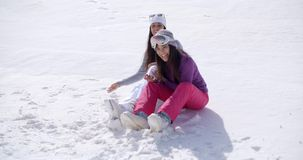 Two young women sitting chatting in the snow. Two young women sitting side by side chatting and laughing in the snow at an alpine ski resort smiling as they stock video