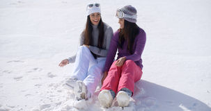 Two young women sitting chatting in the snow Royalty Free Stock Photo