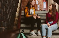 University students chatting during break on campus. Two young women sitting on college steps and talking. Best friends chatting during break in university royalty free stock image