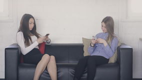 Two young women sitting on couch inside office and holding phones. Beautiful blonde woman, with bright make-up and in blue shirt, texting message to boyfriend stock video