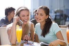 Two young women sitting with drinks in cafe, one talking on mobile phone, smiling Royalty Free Stock Photos