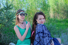 Two young women sitting on grass having good time Royalty Free Stock Image
