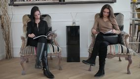 Two young women sitting leaf through magazines. Women sit on chairs in a white room leafing through a books. Young women sitting and looking directories are stock footage