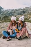 Two young women serve a thermos and a hot cup. stock images