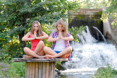 Two young women sitting in meditation yoga position. Two teen girls sitting in yoga position outdoors on summer day near waterfall Royalty Free Stock Photography