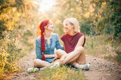 Two best friends spend time in forest. Two young women sitting on the road in forest and laughing royalty free stock images