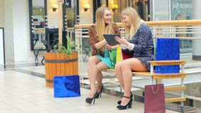 Two young women sitting with shopping bags and stock video footage
