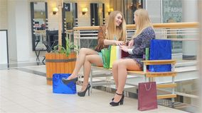 Two young women sitting with shopping bags and stock video