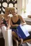 Two young women sitting with shopping bags and smiling. As they inspect their purchases Royalty Free Stock Images