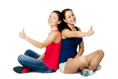 Two young women sitting and showing ok sign Stock Image