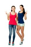Two young women sitting and showing victory sign Royalty Free Stock Photo
