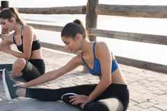 Two women doing stretching exercises at the beach Royalty Free Stock Image