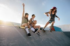 Skateboarding woman riding skateboard at skate park ramp Royalty Free Stock Images