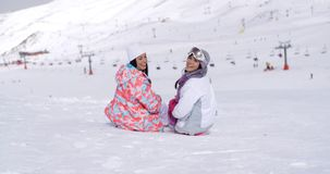 Two young women sitting in snow at a ski resort. Overlooking the ski lift and snow landscape turning to look back at the camera and smile stock video footage