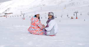 Two young women sitting in snow at a ski resort Stock Photos