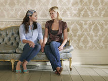 Two Young Women Sitting On Sofa Stock Photography