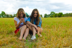 Two young women sitting on summer meadow smiling Stock Photo
