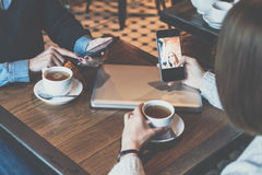 Two young women sitting at table in cafe and using smartphones.Girls shopping online. Royalty Free Stock Images