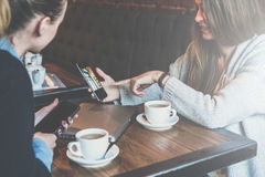 Two young women sitting at table and using smartphones.Woman showing colleague image on smartphone screen. Stock Photo