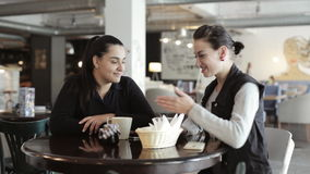 Two young women sitting and talking in cafe. Positive footage of two young women sitting and talking in cafe. Womens in good mood, smiling and laughing stock video