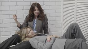 Two young women sitting together on the floor and laughing. Dark haired young woman sitting on the floor. Her blonde friend is lying with her head on girl s laps stock video footage