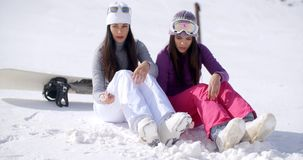 Two young women sitting waiting in the snow stock video