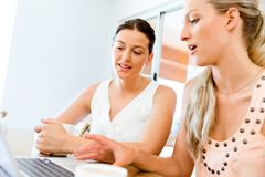Two young women working together at laptop Stock Photo