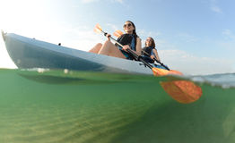 Two young women smiling in blue kayak royalty free stock photos