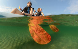 Two young women smiling in blue kayak stock images