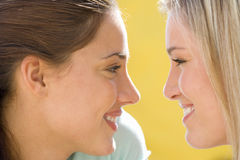 Two young women smiling at each other, close-up, side view Royalty Free Stock Image